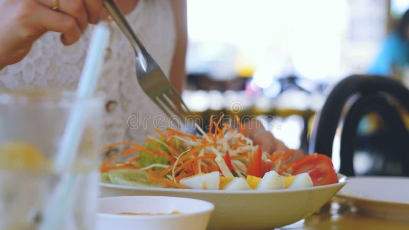 Olio di girasole di versamento della giovane donna nella ciotola di vetro con insalata di verdure con le uova, il cavolo, le caro fotografia stock libera da diritti