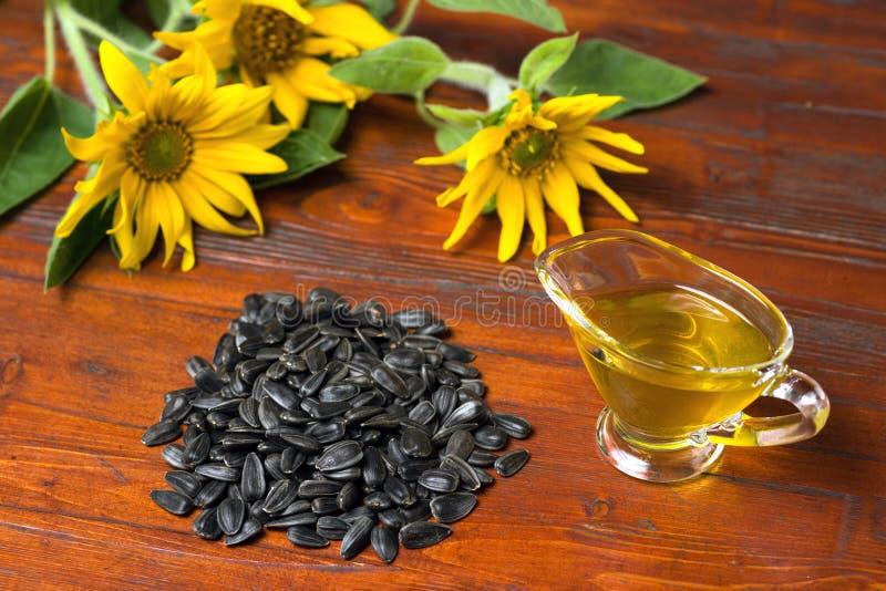 Olio di girasole in un crogiolo di sugo di vetro e una manciata di semi di girasole sui precedenti dei girasoli fotografia stock