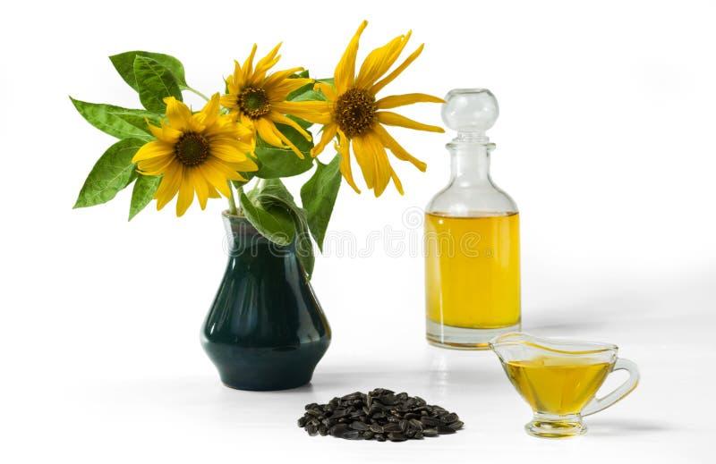 Olio di girasole in un crogiolo di sugo di vetro, in una bottiglia e una manciata di semi di girasole e di girasole in un vaso immagini stock