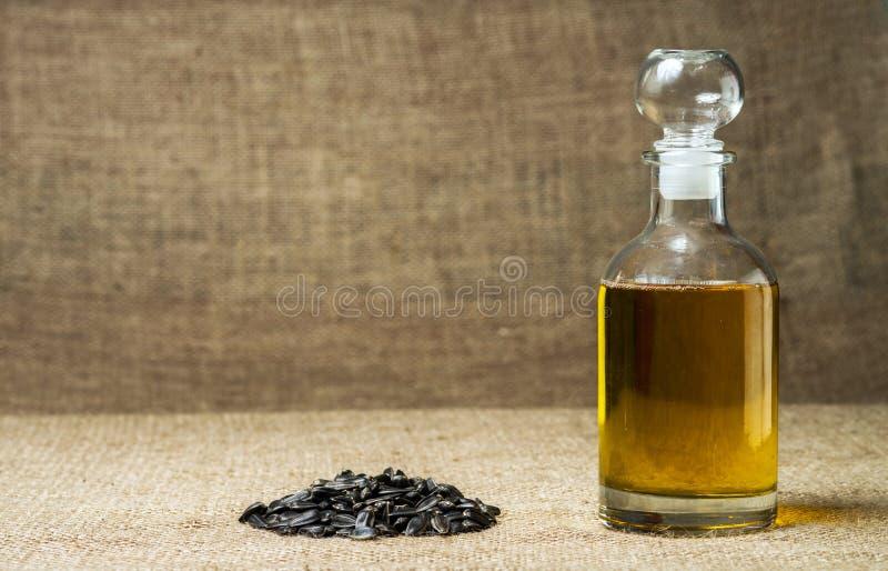 Olio di girasole in un decantatore di vetro, un mazzo di semi di girasole su un fondo di tela da imballaggio fotografie stock libere da diritti