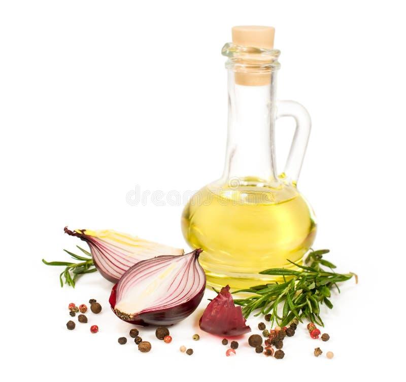 Olio di girasole in una bottiglia con le cipolle rosse ed i rosmarini immagine stock libera da diritti