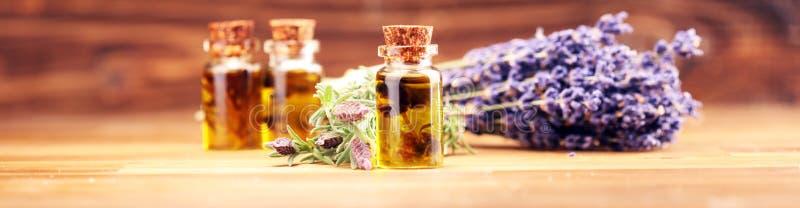 Olio di lavanda essenziale in una bottiglia di vetro su un fondo dei fiori freschi fotografia stock libera da diritti