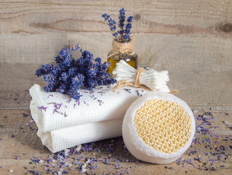 Olio di lavanda, fiori della lavanda ed asciugamani di bianco del bagno immagine stock