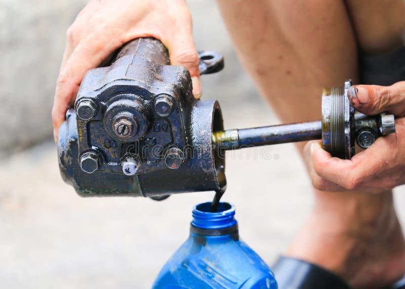 Olio di motore della tenuta della mano del meccanico immagine stock