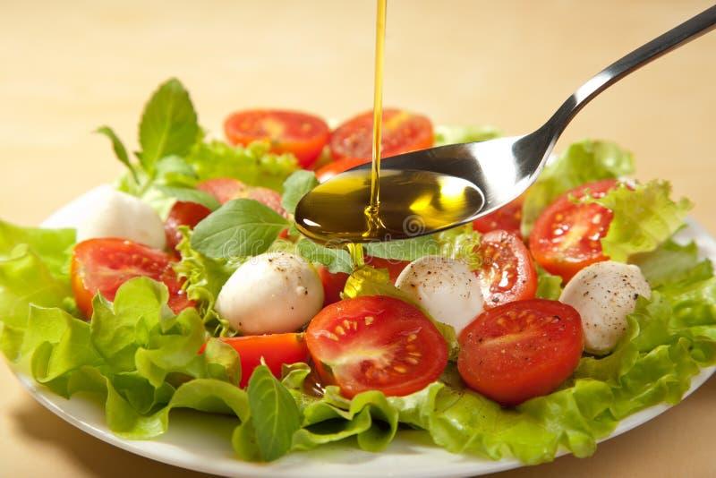 Olio di oliva che versa sopra l'insalata immagine stock
