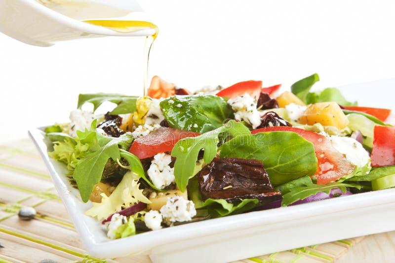 Olio di oliva di versamento su insalata fresca. fotografia stock libera da diritti