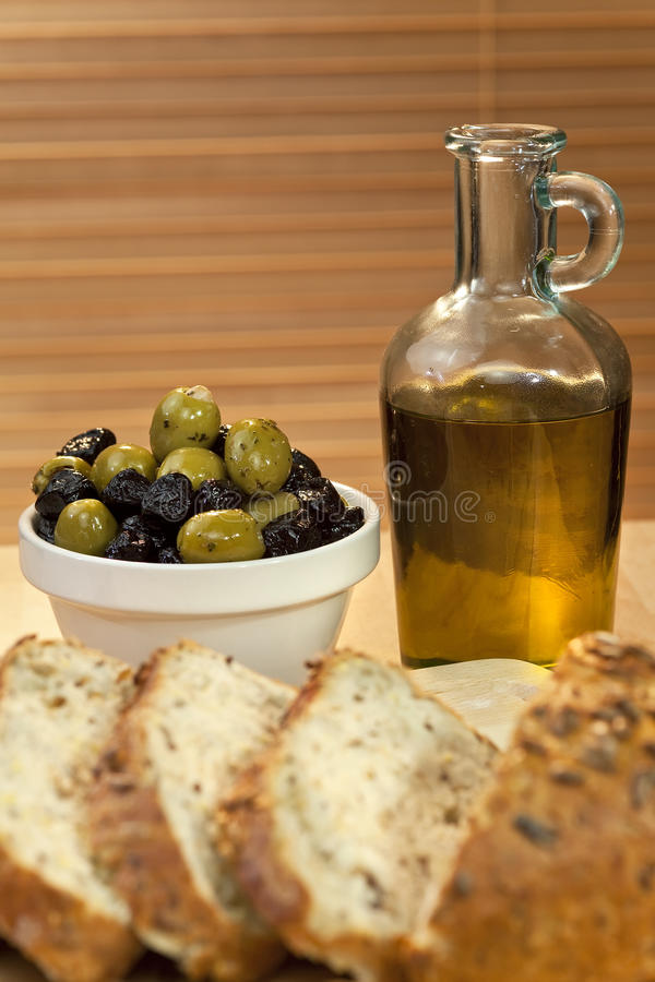 Olio di oliva, olive verdi & nere & pane rustico immagini stock