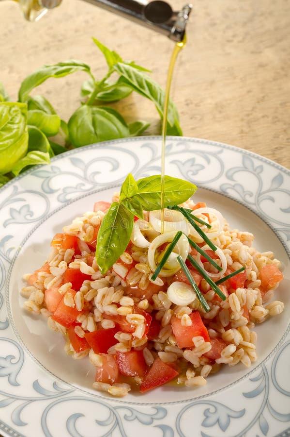 Olio di oliva sopra insalata ortografata immagini stock