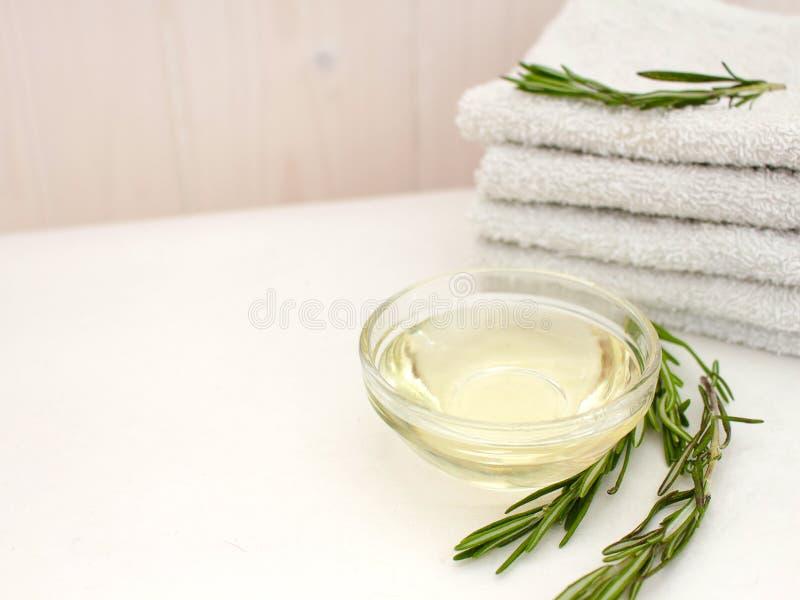 Olio di rosmarino e un ramo dei rosmarini freschi con una pila di asciugamani per cura del corpo e del fronte su un fondo di legn immagine stock