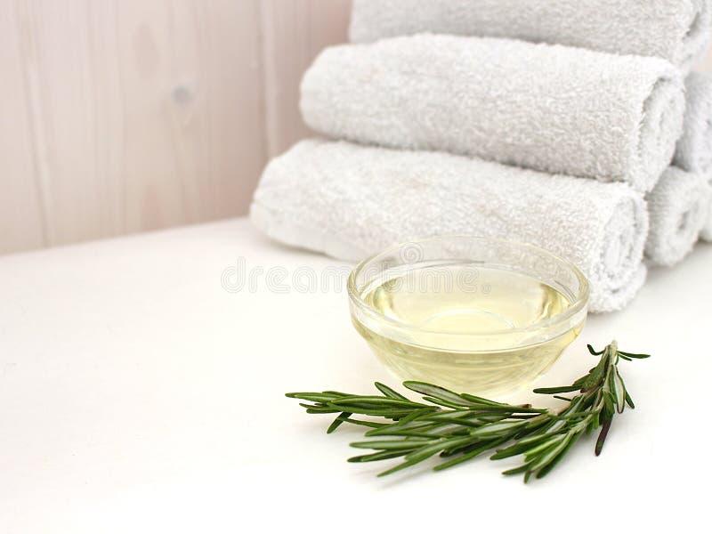 Olio di rosmarino e un ramo dei rosmarini freschi con una pila di asciugamani per il fronte ed il corpo su un fondo di legno dell immagini stock