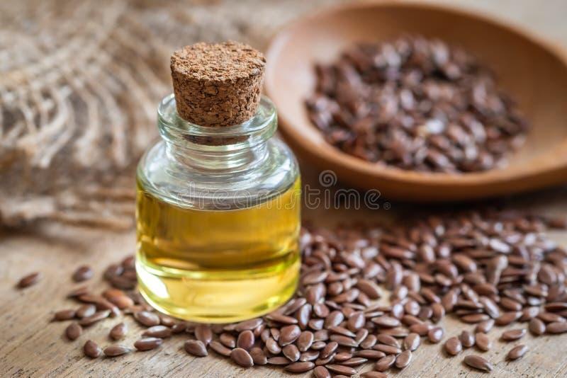 Olio di semi di lino in bottiglia e semi di lino marroni sul cucchiaio di legno fotografia stock