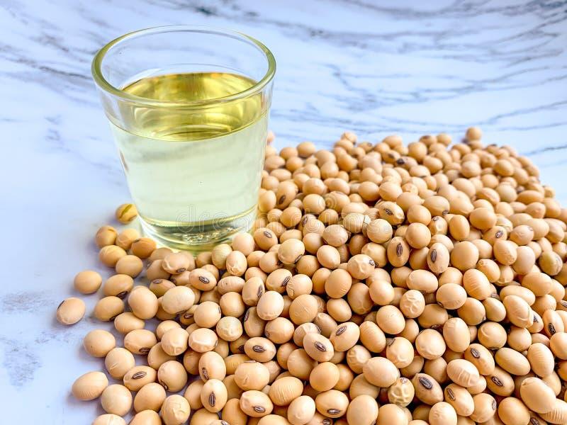 Olio di soia in un vetro disposto accanto alla pila del seme della soia su un fondo bianco immagini stock