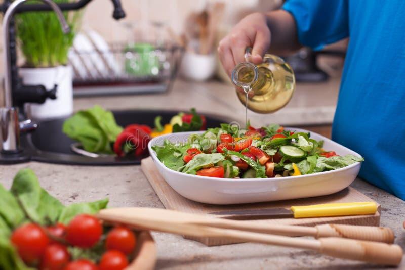 Olio di versamento della mano del bambino su un piatto di insalata misto fresco delle verdure, immagine stock
