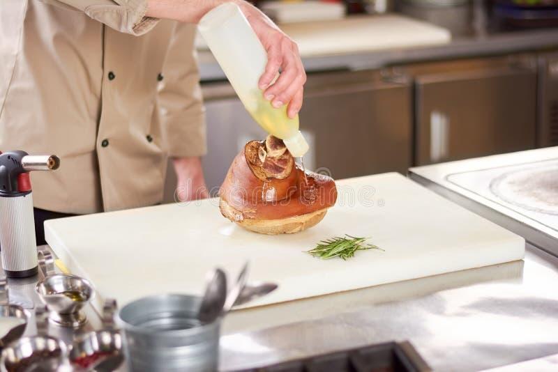 Olio di versamento della mano del cuoco unico sullo stinco dell'agnello immagini stock
