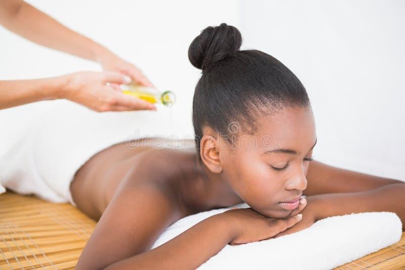 Olio di versamento di massaggio della massaggiatrice su una parte posteriore graziosa della donna fotografia stock