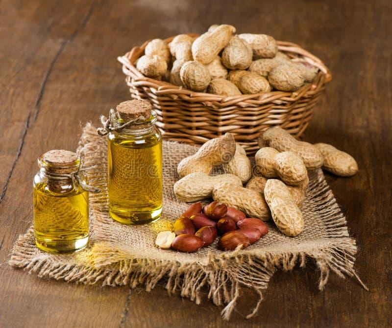 Olio e dadi di arachide su una tavola di legno immagine stock libera da diritti