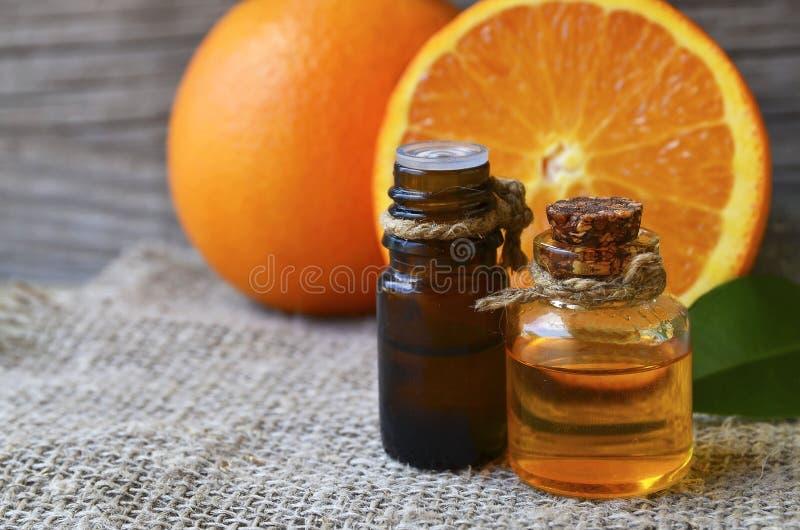 Olio essenziale arancio in bottiglie di vetro per cura di pelle, la stazione termale, il benessere, il massaggio, l'aromaterapia  fotografia stock libera da diritti