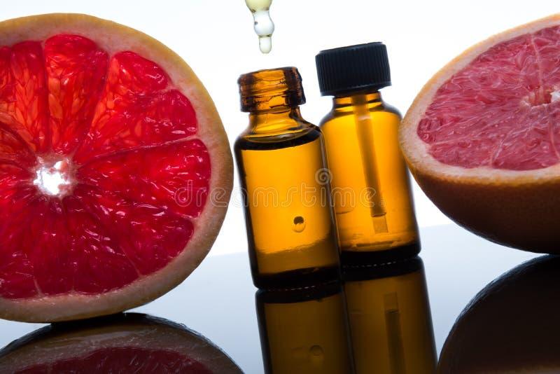 Olio essenziale del pompelmo, estratto, essenza, in bottiglia ambrata con il contagoccia fotografia stock