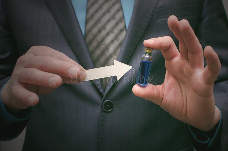 Olio essenziale della pillola blu in mani maschii Giusta scelta dei medicinali fotografia stock
