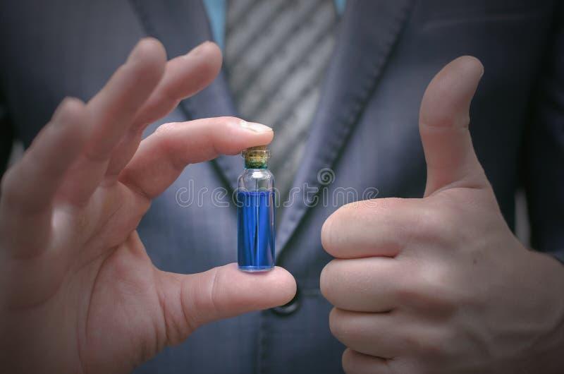 Olio essenziale della pillola blu in mani maschii Giusta scelta dei medicinali immagini stock libere da diritti