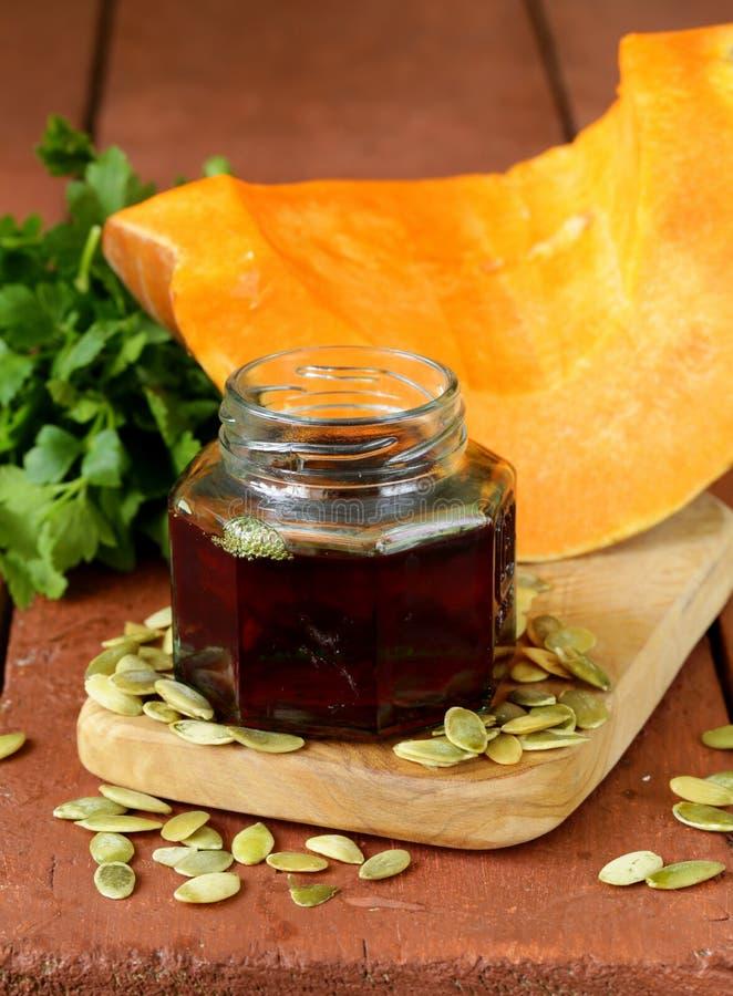 Olio organico della zucca in un barattolo di vetro fotografie stock