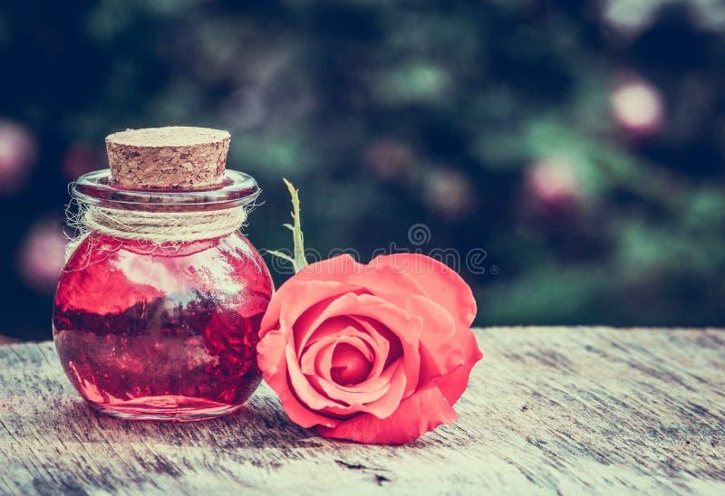 Olio rosa essenziale in una bottiglia di vetro Elisir di amore Pozione di amore fotografia stock