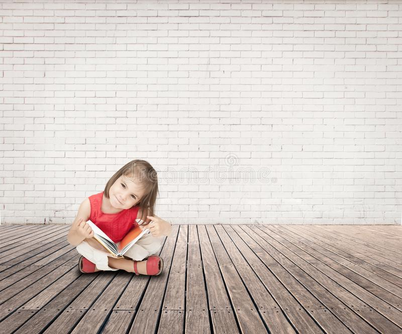 Little girl reading a book on a room stock photo