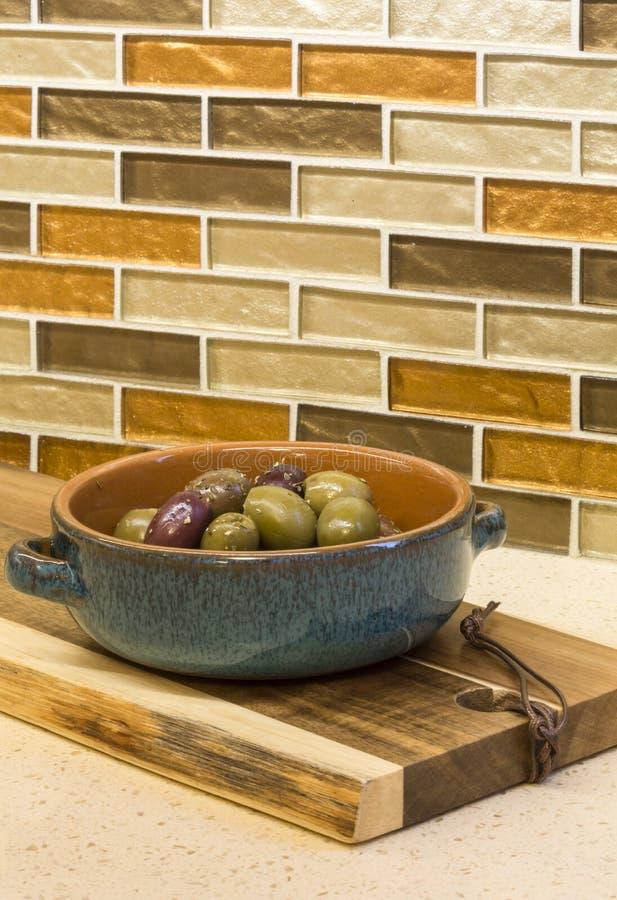 Oliv i bunke och träskärbräda på iscensatt stencountertop med glass backsplash för mosaiktegelplatta i hem- kök royaltyfria bilder