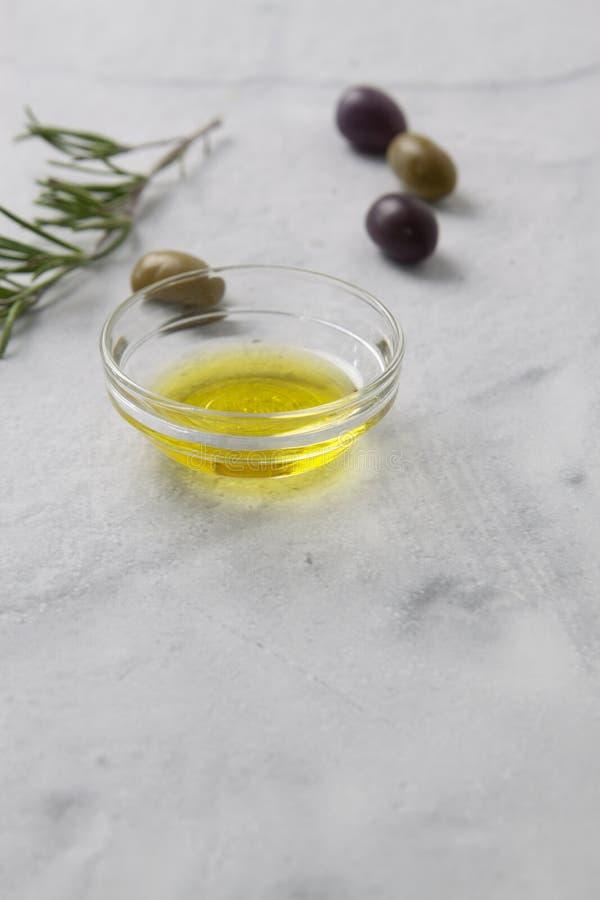 Oliv och olivolja med örter på marmorerar backgound med inskränkt djup av fokusen royaltyfri fotografi