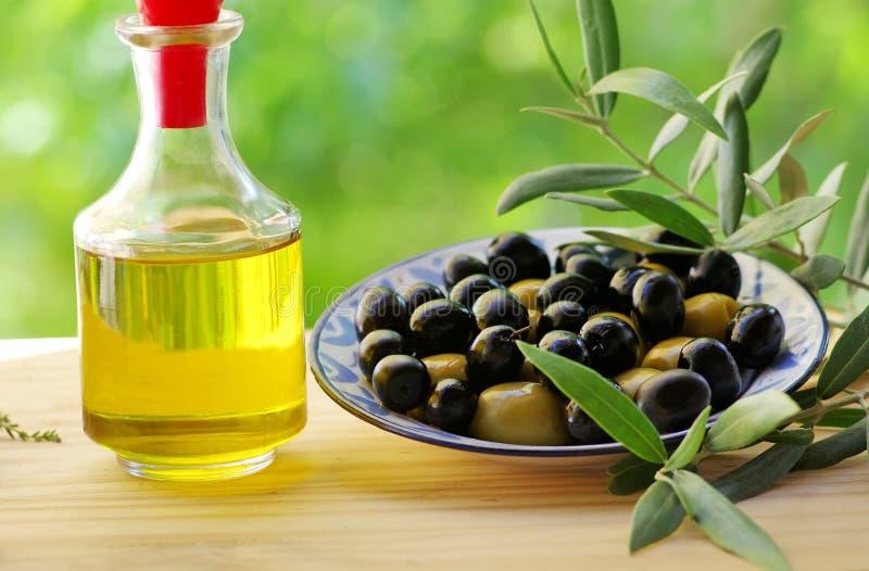 Oliv på plattan och oliveoil arkivfoton
