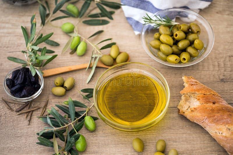 Oliva verde oliva dell'olio con il pane di ciabatta ed oliva nera sopra la o fotografie stock libere da diritti