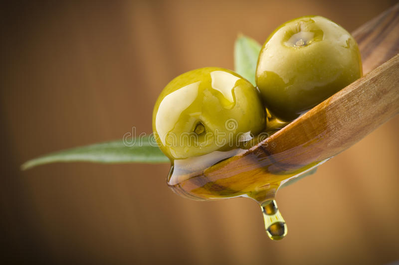 Olive con l'olio di goccia sul cucchiaio di legno fotografia stock libera da diritti