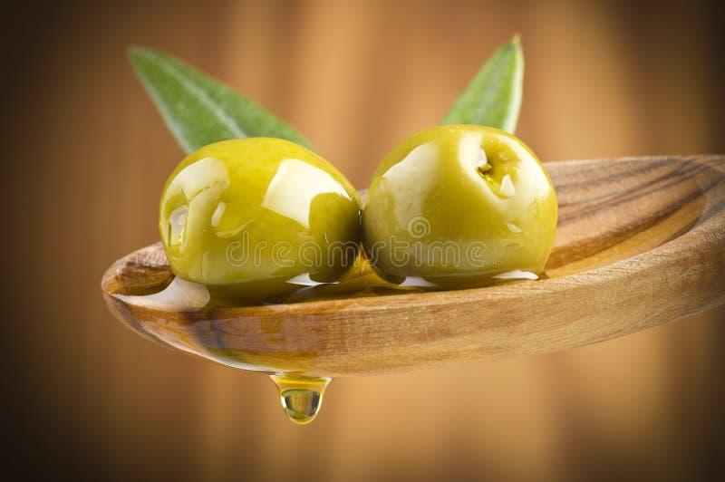 Olive con l'olio di goccia sul cucchiaio di legno immagini stock libere da diritti