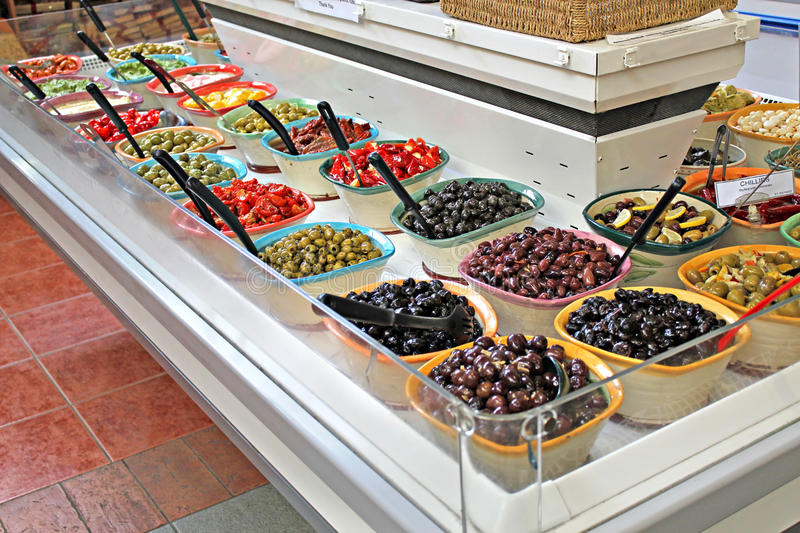 Olive deli bar. Photo of delicious olives from the mediterranian being displayed in a deli indoor market stock image
