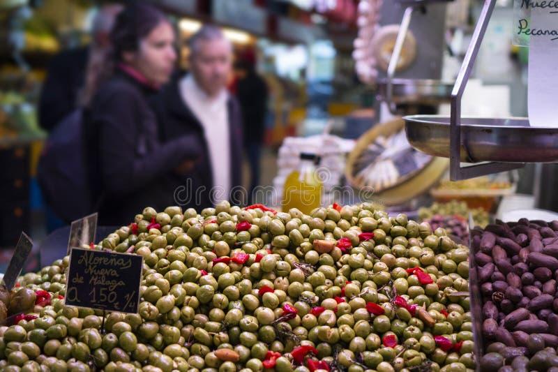 olive di verde dello spanisch con pepe ed aglio marinato da vendere al mercato degli agricoltori in spagna Malaga con i costumers fotografia stock