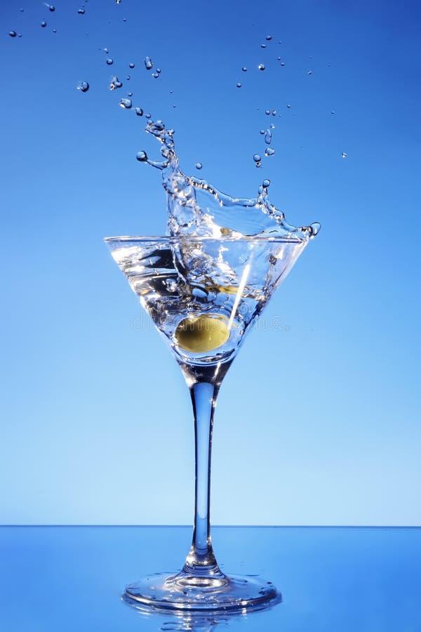 Olive, die in einem Martini-Glas spritzt stockfotos