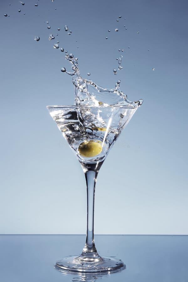 Olive, die in einem Martini-Glas spritzt stockfotografie