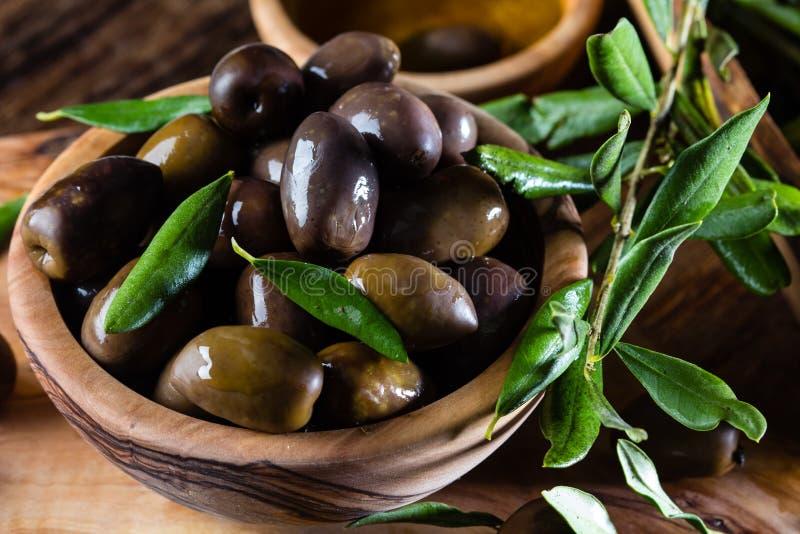 Olive e olio d'oliva in ciotole di legno verde oliva, ramo di olivo fotografia stock