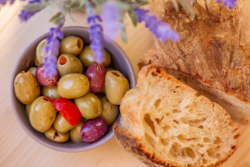Olive farcite, peperone e pane casalingo Olive multicolori in una piccola ciotola su una tavola di legno fotografie stock