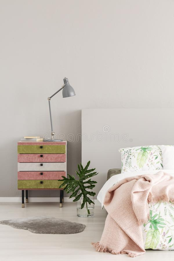 Olive green and pastel pink colored nightstand next to glass vase with leaf in simple bedroom interior, copy space on the empty royalty free stock photo