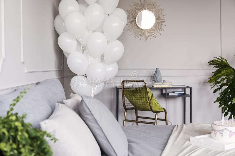 Olive green pillow on fancy golden armchair in chic bedroom with bunch of white balloons, copy space on the empty wall. Green pillow on fancy golden armchair in royalty free stock photos