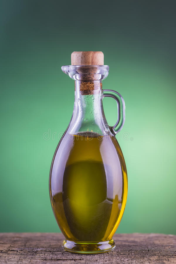 Olive oil bottle with green spotlight background royalty free stock photos