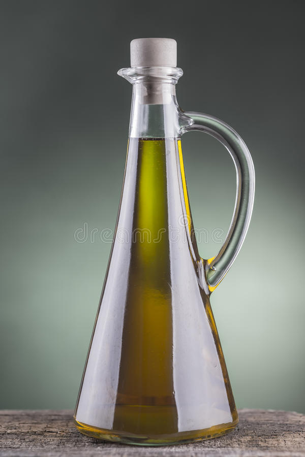 Olive oil bottle with green spotlight background stock photography