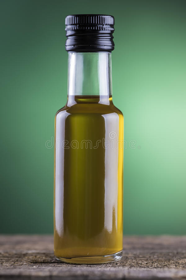 Olive oil bottle with green spotlight background royalty free stock image