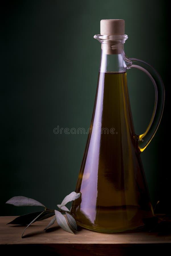 Olive oil bottle with green spotlight background stock image