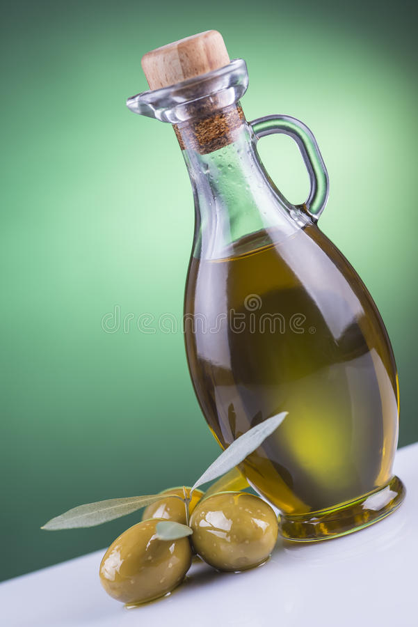 Olive oil bottle and olives on green background royalty free stock image