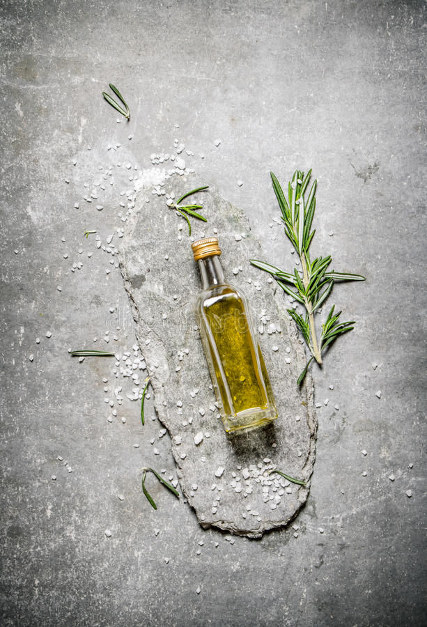 Olive oil in bottle with rosemary and salt. On a stone background stock images