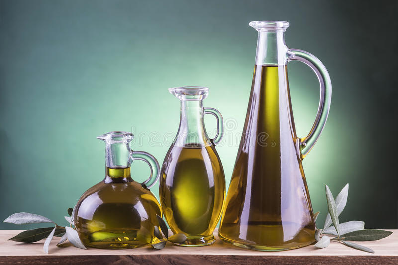Olive oil bottles on a green spotlight background. Three olive oil bottles on a green spotlight background with olive branches stock photos