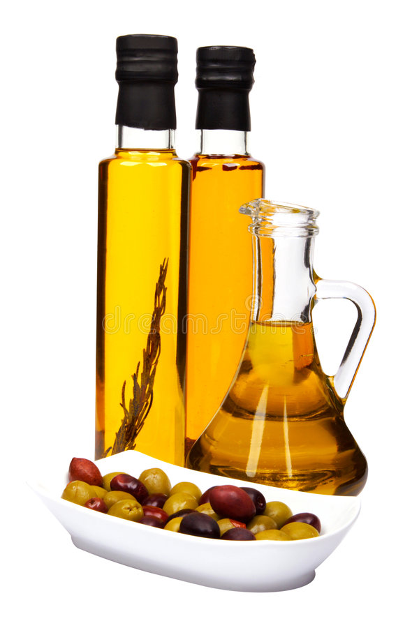 Olive oil bottles and olives. Olive oil bottles: with rosemary, chilli pepper and bottle of pure olive oil. Bowl of mixed olives: black and green royalty free stock image