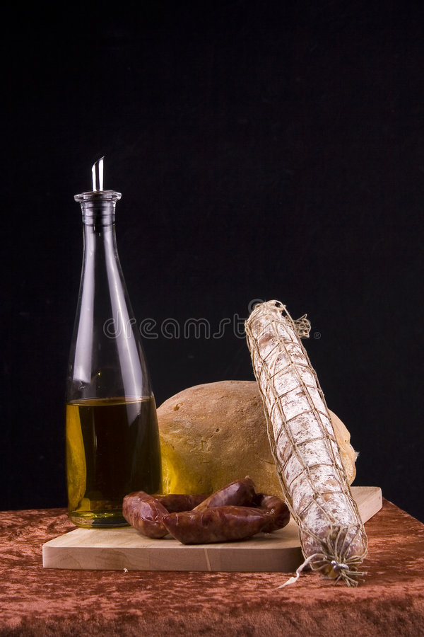 Olive oil, bread, and salami stock image